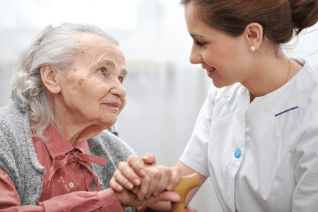 Caregiver holding hands with Eldery Woman