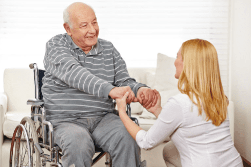Woman holding the hands of a gentleman in a wheelchair